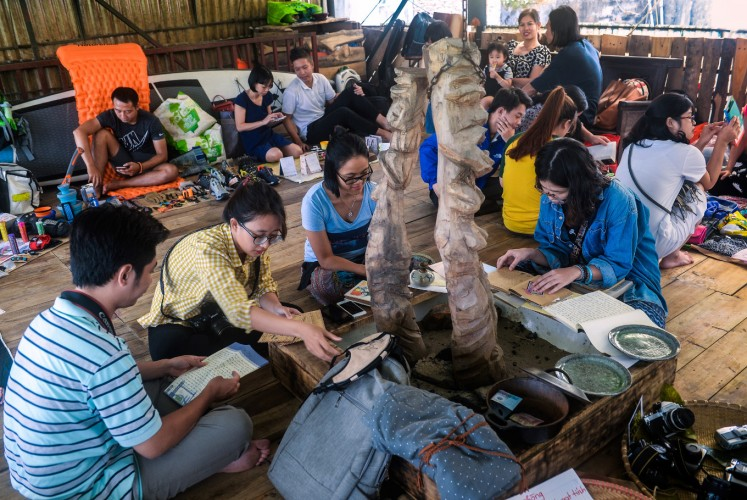In this photograph taken on October 29, 2017, people visiting a once-a-month ex lover's market in Hanoi look for items only on display and which belong to the owner of the market. Shuffling through Vietnam's
