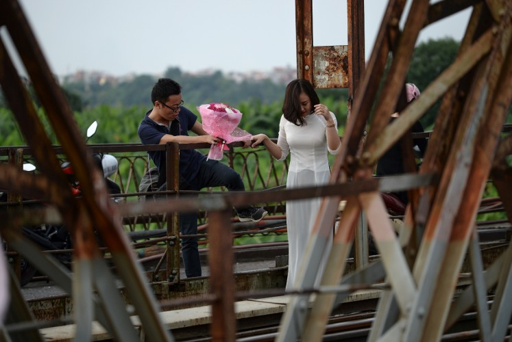 In this photograph taken on October 20, 2017, a man holding a bunch of flowers, climbs over a railing to follow a woman at a century old bridge built by the French and a popular destination for lovers to go and take photographs. Shuffling through Vietnam's