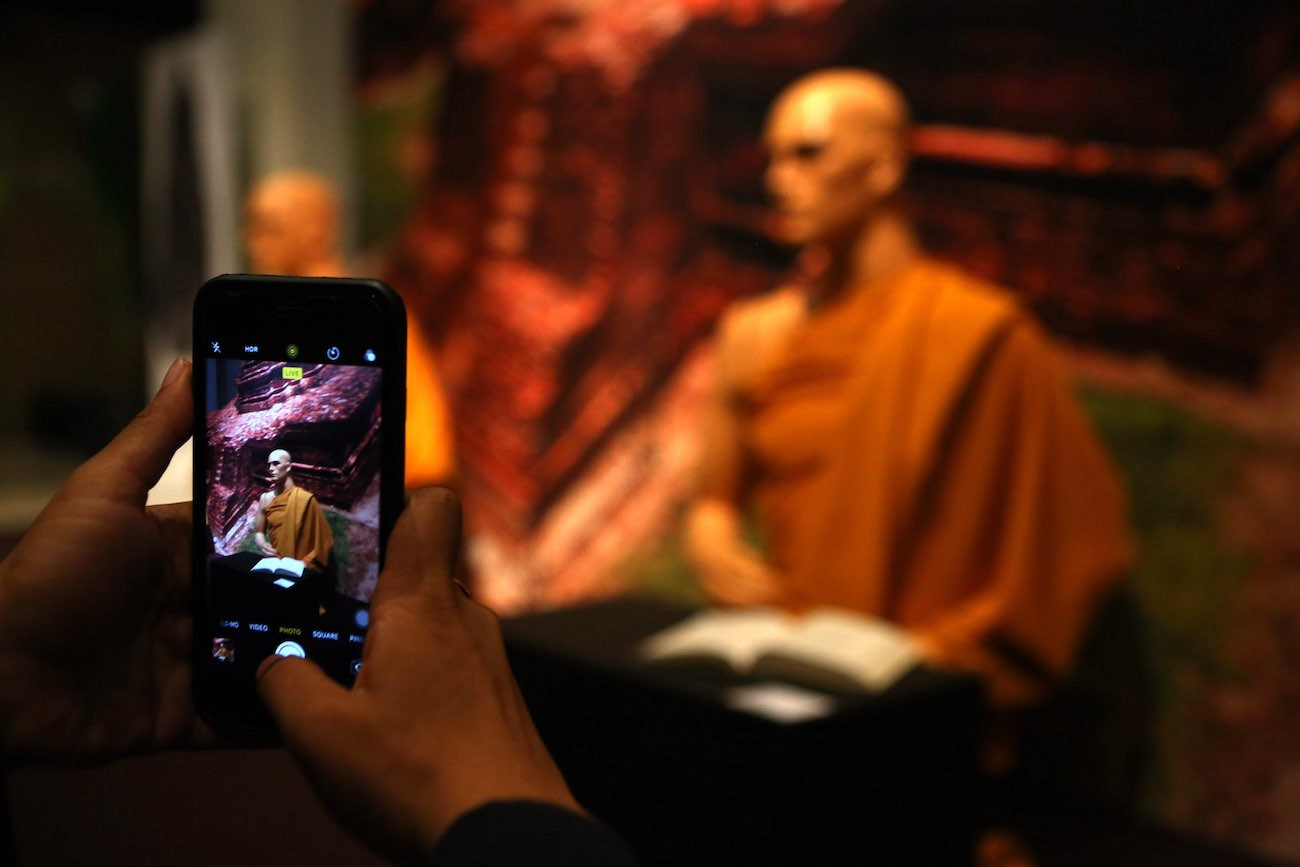 A visitor takes pictures of monks' figurines at the Kedatuan Sriwijaya: The Great Maritime Empire exhibition.