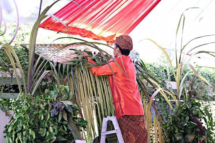President Joko 'Jokowi' Widodo hangs bleketepe (row of plaited coconut leaves) in front of his private residence on Jl. Kutai Utara, Sumber, Surakarta, Central Java, on Nov. 7, 2017.