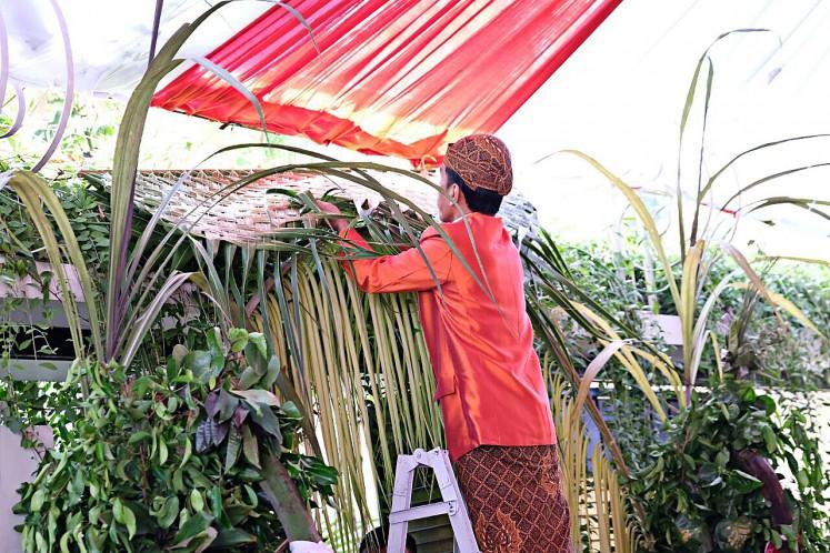 President Joko 'Jokowi' Widodo hangs bleketepe (row of plaited coconut leaves) in front of his private residence on Jl. Kutai Utara, Sumber, Surakarta, Central Java, on Nov. 7, 2017.