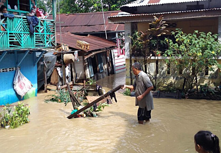 A man lifts up a large piece of debris that was swept by floodwater in Aur subdistrict, Medan Maimon, Medan, North Sumatra, on Tuesday.