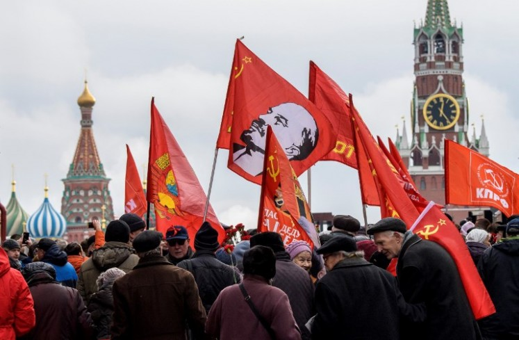 Russian Communist supporters walk along the Red square to lay flowers at Lenin's mausoleum in Moscow on Nov. 5, 2017, to celebrate the forthcoming 100th anniversary of The Bolshevik Revolution. Russia is set to hold low-key events to mark a century since the 1917 Bolshevik Revolution on Nov. 7, with authorities uncertain how to badess the uprising that led to 70 years of Communist rule.