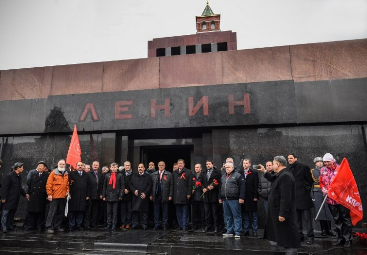 Russian Communists pose for a picture after laying flowers at Lenin's mausoleum on the Red square in Moscow on Nov. 5, 2017, to celebrate the forthcoming 100th anniversary of The Bolshevik Revolution. Russia is set to hold low-key events to mark a century since the 1917 Bolshevik Revolution on Nov. 7, with authorities uncertain how to assess the uprising that led to 70 years of Communist rule.