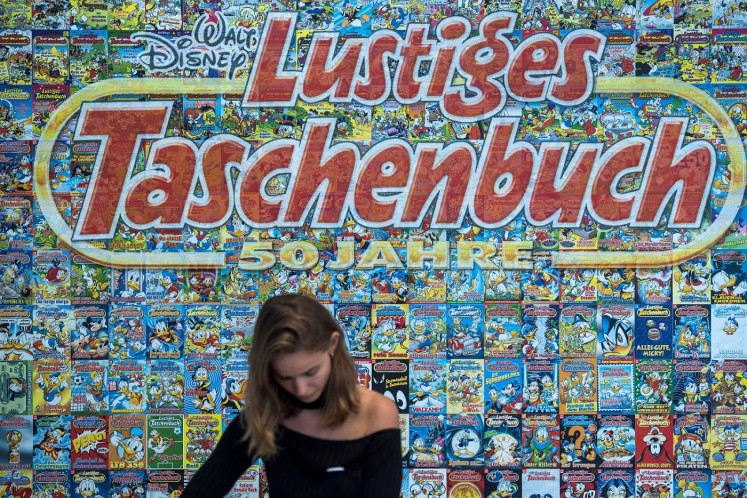 An employee stands behind a cashier desk in front of a backdrop made up of hundreds of covers of Donald Duck pocket books.
