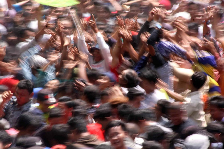 Come and get 'em: Participants grab at thrown apem. JP/ Maksum Nur Fauzan