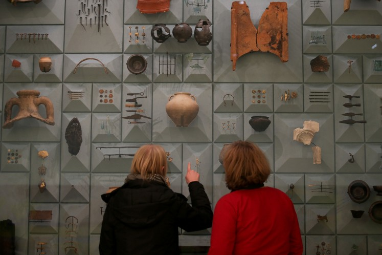 Visitors stand in front of Roman-era items during a press preview at the London Mithraeum.