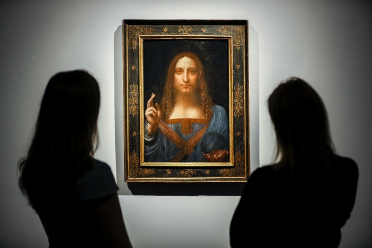 Christie's employees pose in front of a painting entitled Salvator Mundi by Italian polymath Leonardo da Vinci at a photocall at Christie's auction house in central London on October 22, 2017 ahead of its sale at Christie's New York on November 15, 2017.