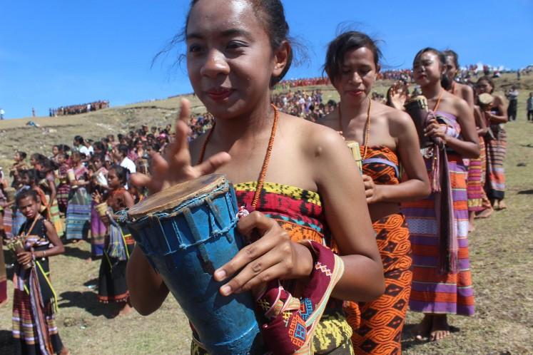 A young female dancer hits a tihar, a small traditional drum, during the Likurai dance. JP/Djemi Amnifu