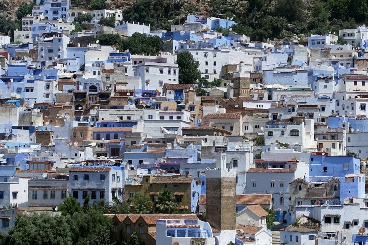A general views shows two minarets amongst houses painted in the traditional blue colour in the northwestern Moroccan city of Chefchaouen, in the Rif mountains, on June 20, 2017.