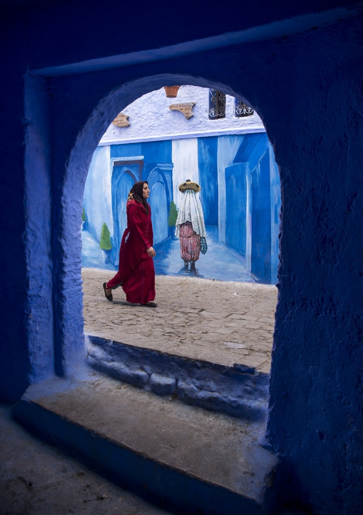 A woman walks in the Medina of the northwestern Moroccan city of Chefchouen, in the northern Rif region, on September 19, 2017.