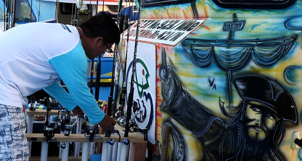 Reel deal: A competitor handles fishing equipment near a mural of Captain Jack Sparrow from the Pirates of the Carribean film series. JP/ PJ Leo