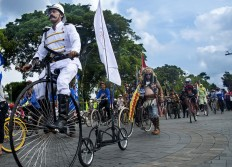 A participant rides a penny farthing, also known as a high wheel, during the Jogja Republik Onthel festival in front of the Vrederburg fortress in Yogyakarta. JP/Tarko Sudiarno