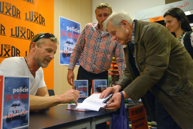 Norwegian author Jo Nesbo (L) signs a copy of the Czech edition of his novel 'Police' ('Policie') at Luxor bookshop in Prague, Czech Republic, on May 04, 2015.