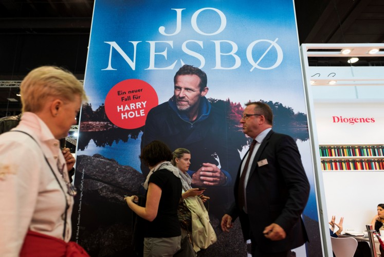 Visitors walk past a poster promoting best-selling Norwegian crime writer Jo Nesbo at the Frankfurt Book Fair on October 13, 2017 in Frankfurt am Main, western Germany. France is this year's guest of honour at the world's largest book fair, where more than 7,000 exhibitors from more than 100 countries are expected from October 11 to 15.