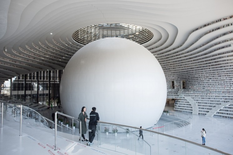 A futuristic Chinese library has wowed book lovers around the world with its white, undulating shelves rising from floor to ceiling, but if you read between the lines you'll spot one problem.