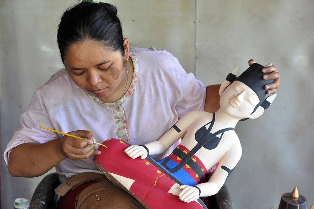 Tukiran's daughter-in-law carefully paints the sculpture of the groom. JP/Magnus Hendratmo