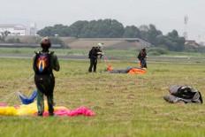 Three parachuters fold their parachutes after landing at the Air Force base. JP/Arya Dipa