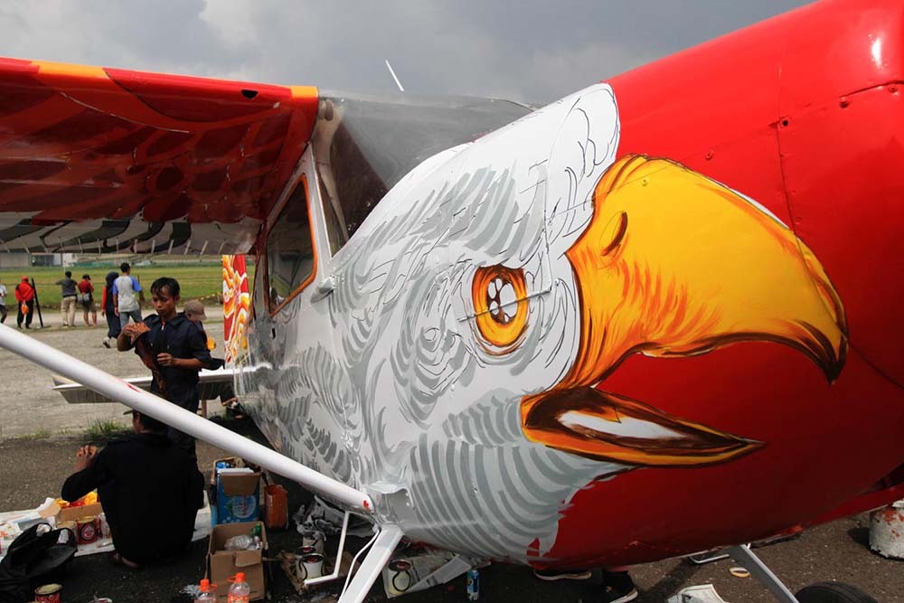 Two artists from painters and designers community draw and paint an airplane during the Bandung Air Show.  JP/Arya Dipa