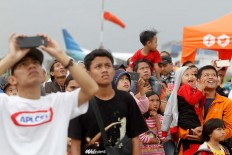 Visitors use their mobile phones to capture the moments during the aerobatic performances at the Bandung Air Show.  JP/Arya Dipa