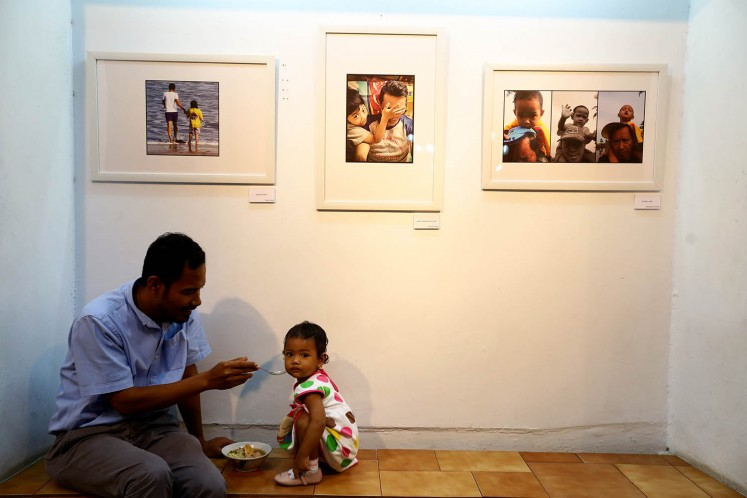 A father poses with his daughter while they are roaming around the venue of 'Ini Ayah Hebatku' photo exhibition on Monday, Nov. 20 at Bentara Budaya, Central Jakarta.