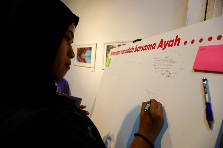 A visitor writes about her most memorable moment with her father on a canvas at 'Ini Ayah Hebatku' photo exhibition on Monday, Nov. 20 at Bentara Budaya, Central Jakarta.