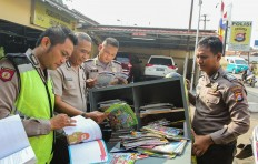 Cap a book: Wahyudin (right) reads books with fellow police officers in Cisoka district before visiting schools with his mobile library. JP/Bangkit Jaya Putra