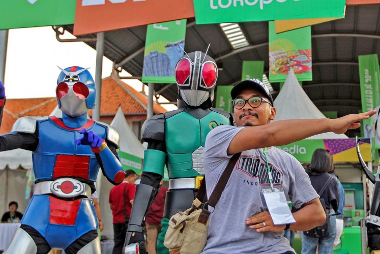 Blast from the past: A visitor poses with characters from the 1990s TV show Ksatria Baja Hitam (Masked Rider Black) during The 90s Festival at JIExpo in Jakarta on Saturday. Currently in its third year, the event celebrates music, games and food popular in the 1990s.