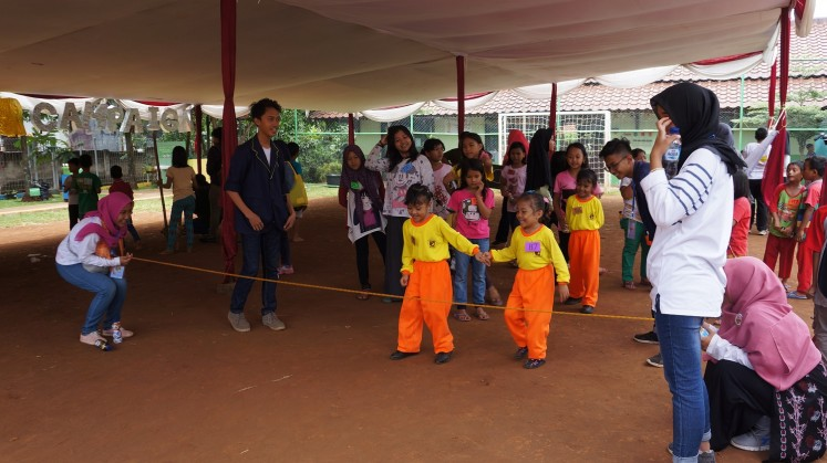 Children play 'lompat tali karet' during the Traditional Games Return Campaign at RPTRA Cililitan in East Jakarta.