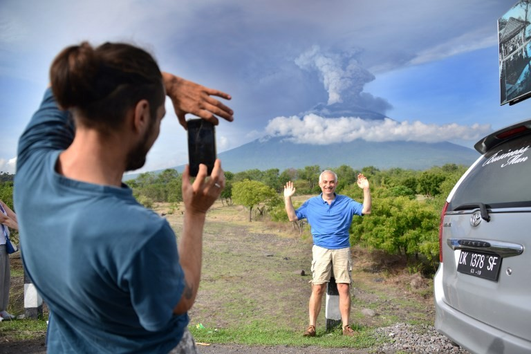 A foreign tourist takes pictures in front of Mount Agung erupting seen from Kubu sub-district in Karangasem Regency, on Indonesia's resort island of Bali on Nov. 27, 2017. Image: Agence France -Presse/Sonny Tumbelaka