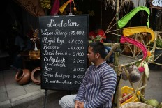 A man sits in front of his food stall selling snacks during the 2017 festival. JP/Aman Rochman