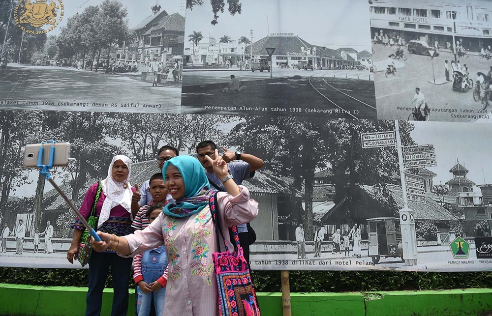 A family takes a selfie with a picture of old Malang in the background during the 2017 festival. JP/Aman Rochman