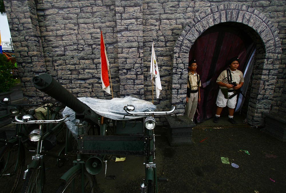 Two children wearing old soldier uniforms stand in front of a replica of Malang Fortress at the 2011 festival. JP/Aman Rochman