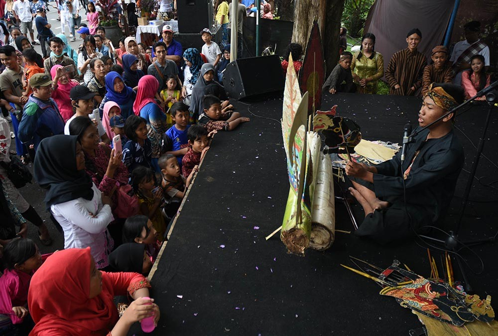 Visitors wearing traditional clothes use their mobile phones to record a performance by a leather puppet performer at the 2017 Malang Tempo Doeloe Festival on Nov. 12. 2017. JP/Aman Rochman