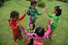 Riddle me this: Four girls play a traditional guessing game during the Ajar Pusaka Budaya event. JP/ Aman Rochman