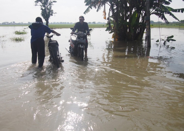 In crisis: Residents wade through a flooded road in Gadingan village, Mojolaban, Sukoharjo, Central Java, on Nov.29.