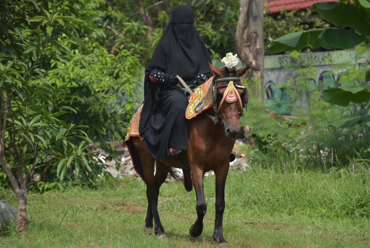 This picture taken on November 12, 2017 shows an Indonesian Muslim woman riding a horse in Bekasi. Riding a horse or nailing an archery target is tough at the best of times -- it's even harder when you're wearing a niqab. But that isn't about to stop a group of Indonesian women who have banded together as they face prejudice against the face-covering veil at the centre of a heated global debate over religious freedom and women's rights.