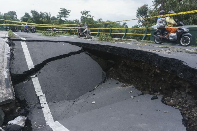 Locals pass through a collapsed bridge on motorcycles in Imogiri, Bantul regency, Yogyakarta, on Thursday.