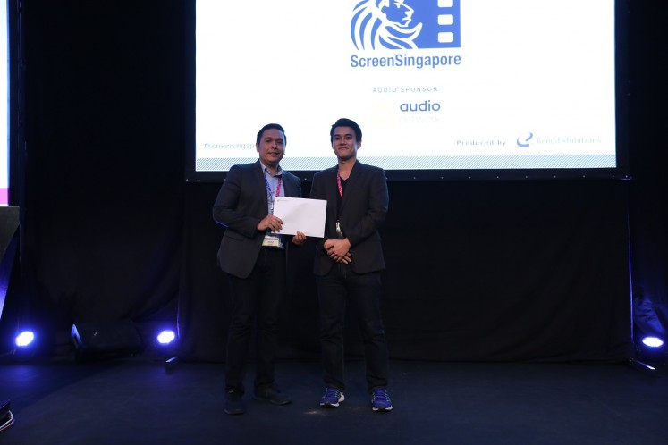 'The Hunted' producer Delon Tio (left) receives the award at the third Southeast Asian Film Financing (SAFF) Project Market in Singapore on Dec. 1.