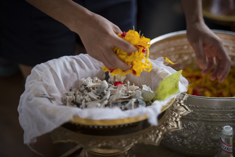 This photo taken on November 5, 2017 shows the bones and ashes of a pet dog being covered in flowers, before being released in the Chaopraya river in Bangkok. Pet cremations, complete with Buddhist rituals, are popping up across Bangkok for dogs, cats and even monkeys. In a devout Buddhist kingdom where religion and superstitious beliefs entwine, some pet owners believe the monk-led send off will boost their pets' chances of being reincarnated as a higher being.