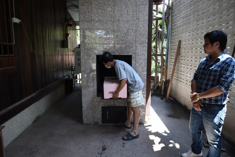 This photo taken on September 14, 2017 shows an undertaker placing the coffin of Dollar, a six-year-old Shih Tzu dog, inside the crematorium during the pet's funeral at Wat Krathum Suea Pla Buddhist temple in Bangkok. Pet cremations, complete with Buddhist rituals, are popping up across Bangkok for dogs, cats and even monkeys. In a devout Buddhist kingdom where religion and superstitious beliefs entwine, some pet owners believe the monk-led send off will boost their pets' chances of being reincarnated as a higher being.