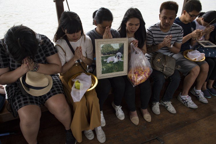 This photo taken on November 5, 2017 shows mourners praying for their pets before releasing their bones and ashes in the Chaopraya river in Bangkok. Pet cremations, complete with Buddhist rituals, are popping up across Bangkok for dogs, cats and even monkeys. In a devout Buddhist kingdom where religion and superstitious beliefs entwine, some pet owners believe the monk-led send off will boost their pets' chances of being reincarnated as a higher being.