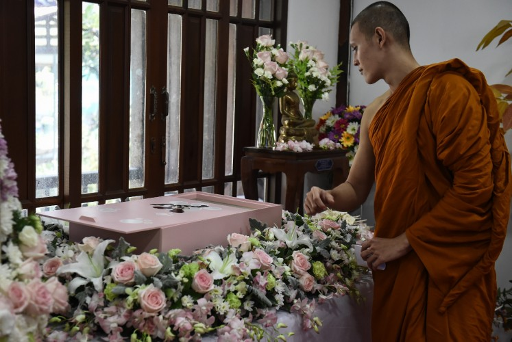 This photo taken on September 14, 2017 shows a Buddhist monk blessing the body of Dollar, a six-year-old Shih Tzu dog, during the pet's funeral at Wat Krathum Suea Pla Buddhist temple in Bangkok. Pet cremations, complete with Buddhist rituals, are popping up across Bangkok for dogs, cats and even monkeys. In a devout Buddhist kingdom where religion and superstitious beliefs entwine, some pet owners believe the monk-led send off will boost their pets' chances of being reincarnated as a higher being.