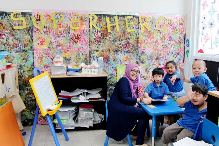 Fun day: Children and their teacher pose during a classroom activity at Saraswati Learning Center in Cempaka Putih, Central Jakarta.
