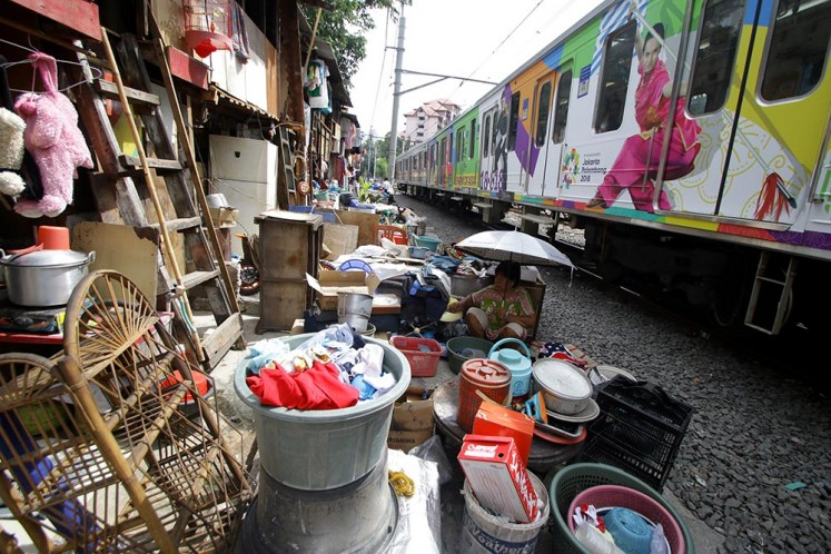 A resident sits in front of her house in a densely populated area near the railway in Central Jakarta.