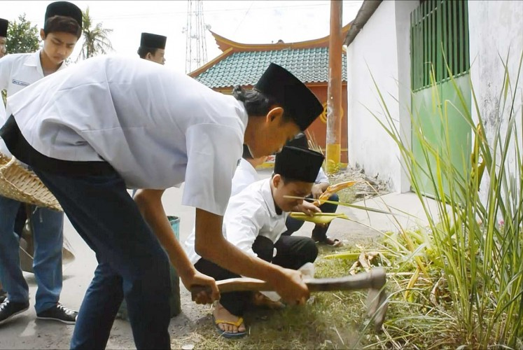 Helping the community: Kauman Islamic Boarding School students work together to clean up the surrounding neighborhood, which is predominantly ethnic Chinese.