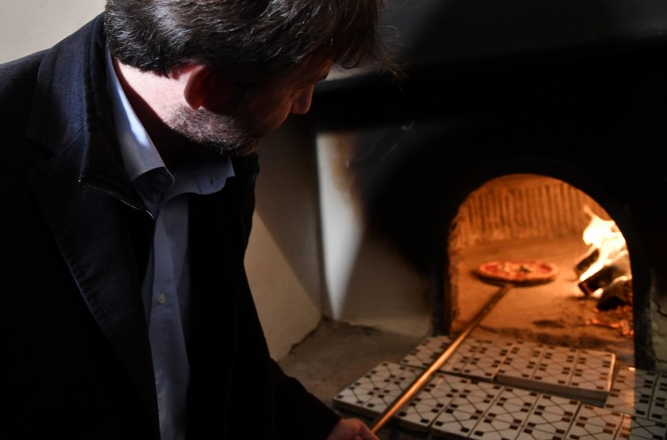 Italy's Culture Minister Dario Franceschini takes out a pizza from the first stone oven where was cooked a Pizza Margherita, on December 6, 2017 at the Capodimonte museum in Naples.