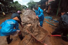 Villagers work together to clean up thick mud covering the road connecting Imogiri and Siluk villages in Bantul regency. JP/Aditya Sagita