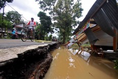 Villagers pass by a house destroyed by floods in Dogongan village, Imogiri district, in Bantul regency, Yogyakarta, on Wednesday Nov. 29, 2017. JP/Aditya Sagita