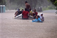 Villagers use a rubber dinghy to pass through chest high flood waters, in Gunungkidul regency. Heavy rains inundated the area in up to two meters of water. JP/Aditya Sagita